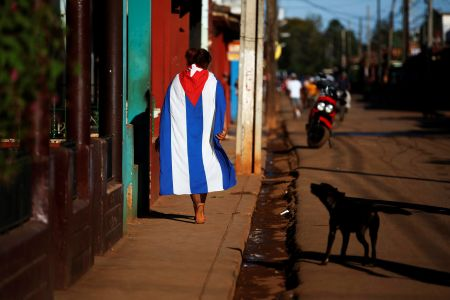A dog barks at a person wearing a Cuban flag in the town of Alquizar